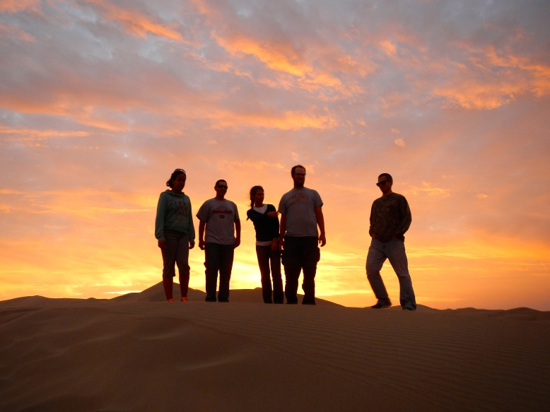 The sun setting over a sand dune in Huacachina.